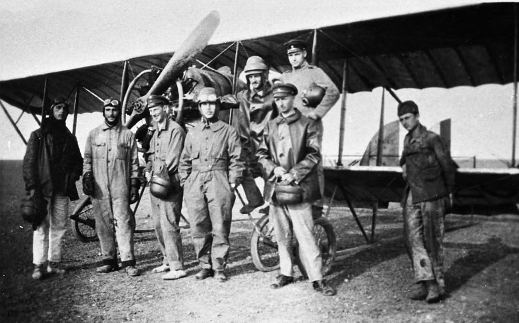 """Opettaja Aldeguerin oppilaista Istres'ssa kesällä 1919. Vänrikki Asser Järvinen lentohaalareissa ja kypärä päässä koulukone Caudron G.3:n potkurin lavan alla. Kaksitasoinen ja yksimoottorinen tiedustelukone oli helppo lentää ja korjata. Se oli käytössä 1910- ja 1920-luvulla Ranskan lisäksi useassa maassa. Suomessa """"Tutankhamoneita"""" oli ilmavoimien käytössä kaikkiaan 19 kappaletta vuosina 1920-1924. Kuva: Keski-Suomen Ilmailumuseo"""