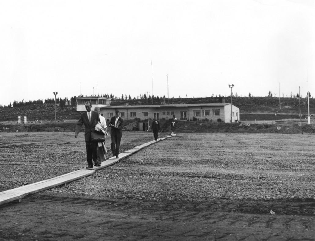 Lentomatkustajia Rovaniemen lentoasemalla luultavasti loppukesästä 1960. Liikennealueen remontin ja kestopäällysteen lisäämisen takia jouduttiin turvautumaan puiseen kävelysiltaan. Taustalla vuonna 1953 valmistunut järjestyksessään kolmas lennonjohto- ja matkustajarakennus. Esko Manninen, LF-Foto Oy / Suomen Ilmailumuseo.