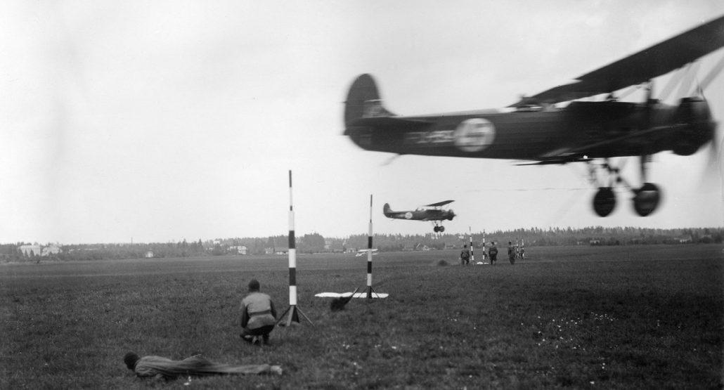 """Fokker C.V -laivue viestinsieppauksessa Suur-Merijoen lentonäytöksessä 3.8.1935. Tähystäjä sieppasi 4-5 metrin korkuisten tolppien välissä olevan köysisilmukan joko alaslasketulla koukulla tai """"naaralla"""". Silmukan alareunassa oli metallinen viestikotelo, joka oli merkittävin yhteydenpitoväline lentokoneen ja maan välillä 1930-luvulla."""
