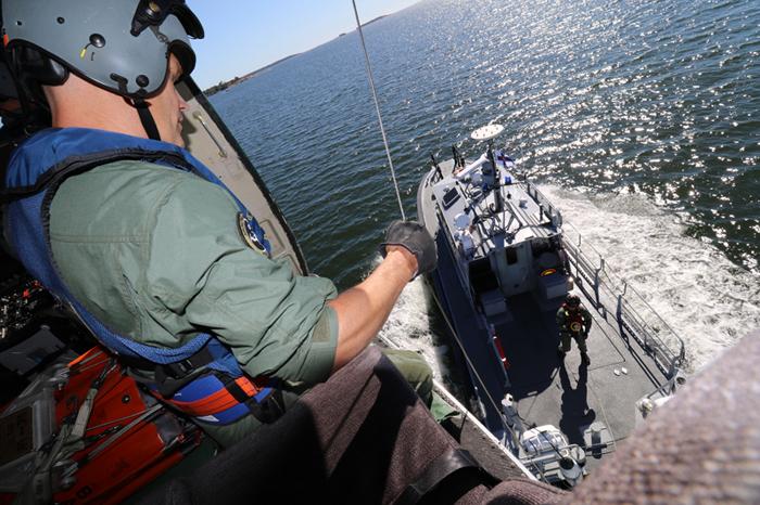 Res. ylirajavartija Jari Laaksonen auttaa vanhemman merivartijan, pintapelastaja Sami Ollilan vinssiin ja partioveneen kannelle 17.8.2015 harjoituksissa.