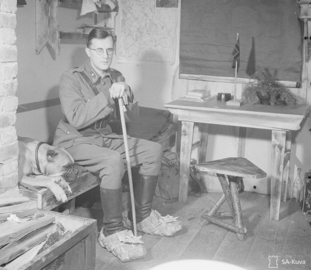 """SA-kuva tammikuulta 1943: """"Välähdyksiä erään komppanian puhdetyöharrastuksista. Vänrikki on saanut pojiltaan syntymäpäivälahjaksi tuohiset kalossit, joilla on sekä kokoa että näköä. Keppi on komppanianpäällikölle annettu joululahja, sekin hienoa kotityötä samoin kuin lipputanko pöydällä. Tsopina."""""""